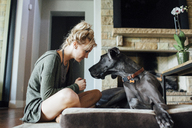 Woman looking at Great Dane while sitting at home - CAVF46342