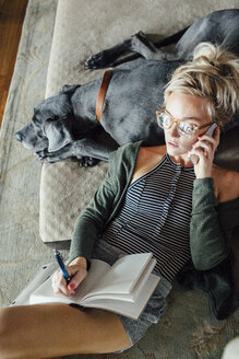 Overhead view of woman talking with diary using smart phone while relaxing on Great Dane at home - CAVF46348