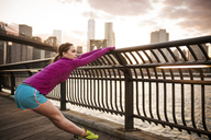 Woman stretching at railing by river in city - CAVF46456