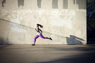 Woman jogging on street by wall - CAVF46498