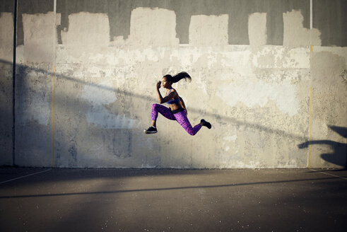 Side view of sportswoman jumping in mid-air against wall - CAVF46504
