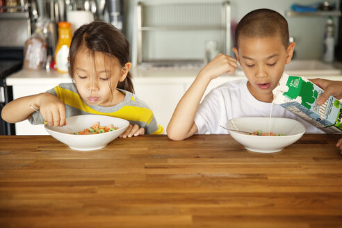 Siblings having breakfast at wooden table in kitchen - CAVF46699