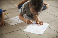 Girl drawing on paper while lying besides brother on floor at home - CAVF46711