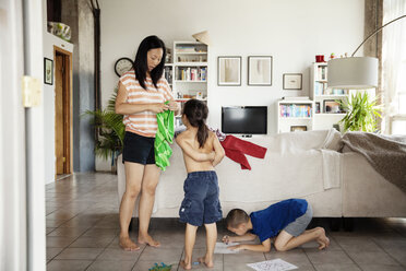 Mother wearing t-shirt to daughter while son drawing on paper at home - CAVF46714