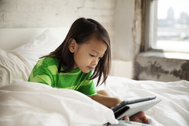 Smiling girl using tablet computer while resting on bed at home - CAVF46717