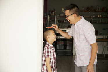 Father measuring son's height at home - CAVF46729