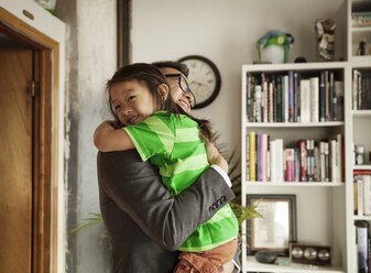Happy father embracing daughter while standing in living room at home - CAVF46732