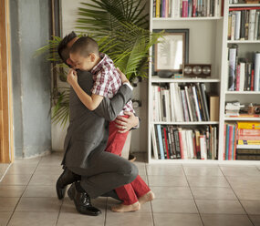 Father embracing son by bookshelf in living room - CAVF46735
