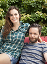 Portrait of couple sitting on chair in lawn - CAVF46852