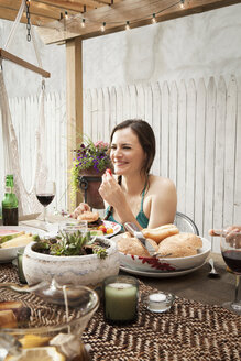 Woman eating food while sitting at table in yard - CAVF46861
