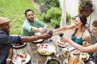 High angle view of friends toasting wineglasses while sitting at table in yard - CAVF46867