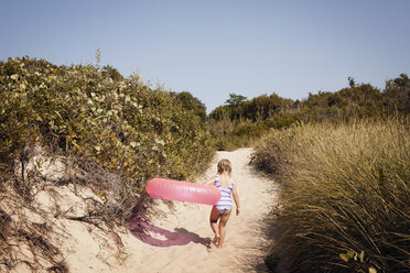 Rear view of girl carrying inflatable ring while walking on sand - CAVF46900