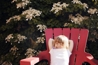Cute girl relaxing on lounge chair at yard - CAVF46912