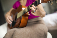 Midsection of woman playing guitar at home - CAVF47014