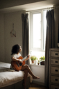 Woman looking away while playing guitar at home - CAVF47020