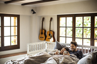 Smiling couple using smart phones while lying on bed at home - CAVF47049