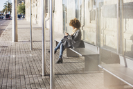 Woman using smart phone while sitting on seat at bus stop - CAVF47091