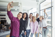Happy business people taking selfie while standing by window in office - CAVF47229