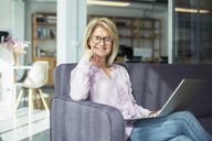 Portrait of confident businesswoman with laptop computer sitting on sofa in office - CAVF47253