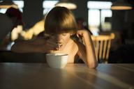 Shirtless boy eating breakfast at table - CAVF47286