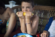 Close-up of boy eating corn while sitting friends on sofa - CAVF47295