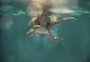 Carefree girl wearing goggles while swimming underwater in pool - CAVF47316