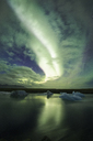 Tilt image of Aurora Borealis over frozen lake - CAVF47340