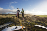 Surfers looking away while standing on grassy field against sky - CAVF47343