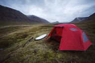 Tent and surfboard on grassy field against cloudy sky - CAVF47346