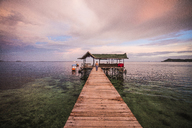 Distant view of woman on pier against cloudy sky - CAVF47349
