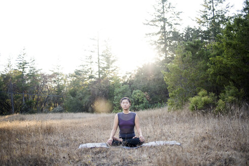 Woman meditating while sitting on exercise mat against clear sky at field - CAVF47376