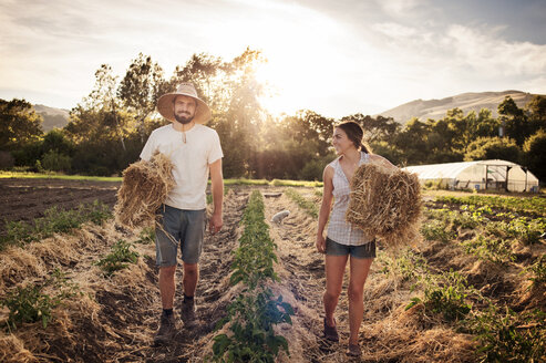 Happy farmers carrying hay bales while walking on field - CAVF47415