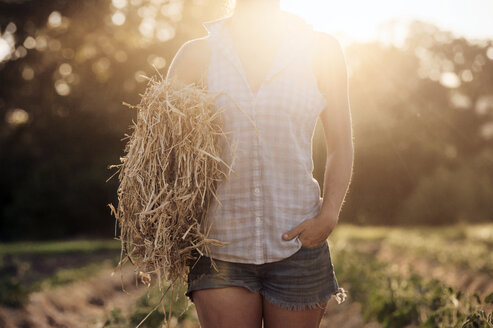 Midsection of female farmer holding hay bale on field - CAVF47418