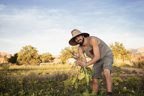 Portrait of happy male farmer holding freshly harvested beetroots on field against sky - CAVF47442