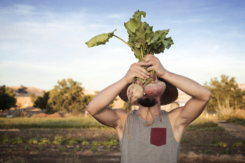 Male farmer holding freshly harvested beetroots in front of face at field - CAVF47445