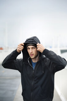 Portrait of confident male athlete wearing hooded jacket on Bay Bridge - CAVF47472