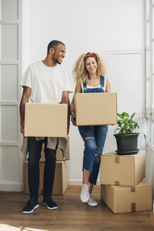 Happy couple carrying cardboard boxes while standing on floor at new house - CAVF47589