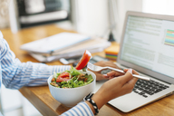 Cropped image of woman holding fork with tomato slice by laptop computer at wooden table - CAVF47601