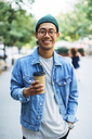 Portrait of happy man with hand in pocket holding disposable cup at sidewalk - CAVF47694