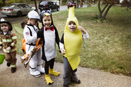 Cheerful children in Halloween costumes standing on pathway during trick or treating - CAVF47784