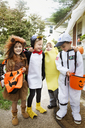 Full length of happy children in Halloween costumes standing at yard during trick or treating - CAVF47787