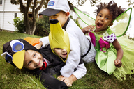 Happy children in Halloween costumes playing on grass - CAVF47796