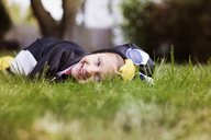 Portrait of smiling girl in Halloween costume lying on lawn - CAVF47802