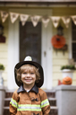 Portrait of smiling boy in Halloween costume standing against house - CAVF47805