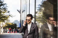 Smiling businessman using phone reflecting on glass building in city - CAVF47817