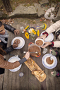 High angle view of woman serving curry to friend at wooden table outdoors - CAVF47868