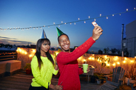 Happy friends taking selfie through mobile phone on building terrace at birthday party - CAVF47892