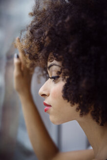 Close-up of thoughtful woman with curly hair looking through window - CAVF47916