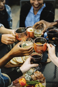 Cropped image of happy friends toasting drinks in backyard - CAVF47998