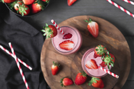 Glasses of strawberry smoothie and strawberries on dark wood - RTBF01197